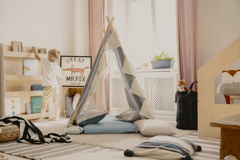 Real photo of a scandi playroom interior with a tent and pillows. Boy putting a toy on a shelf. Real photo of a scandi playroom interior with a tent and pillows stock photos