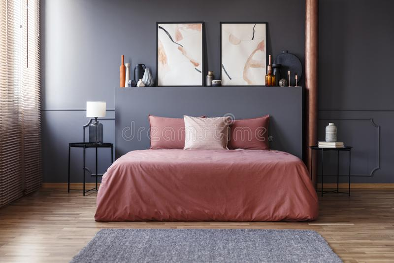 Real photo of a simple bedroom interior with dirty pink bedding. On the bed standing against dark gray wall with molding, between two, metal bedside tables stock photography