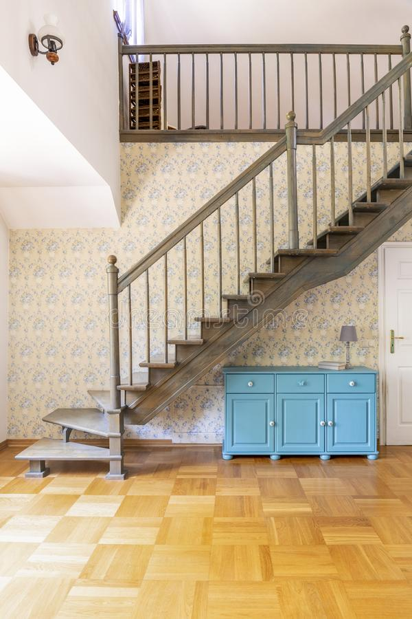 Real photo of a simple corridor with gray, wooden stairs, blue c stock images
