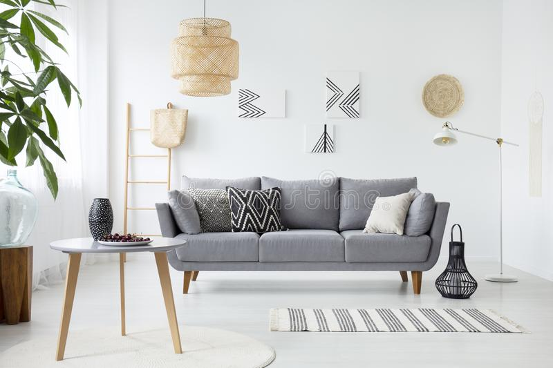 Real photo of a simple living room interior with cushions on gray sofa, paintings on white wall and cherries on a coffee table stock photo