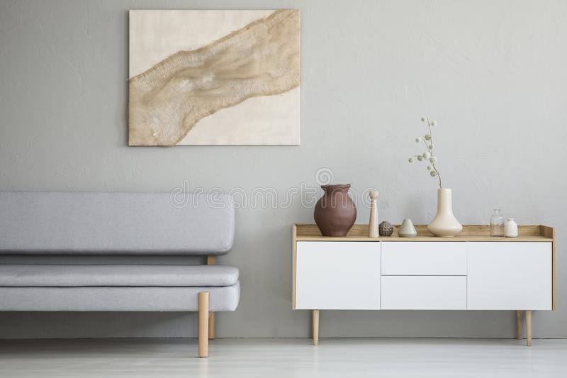 Real photo of a simple living room interior with a natural paint. Ing on the wall and gray sofa next to a wooden cupboard stock photos