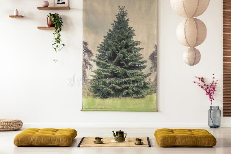 Real photo of a tatami mat with a pot and teacups in a japanese. Room interior with big tree poster on a wall stock photography