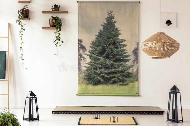 Real photo of a tatami mat between two black lanterns in oriental apartment interior with tree graphic on the white wall stock photos