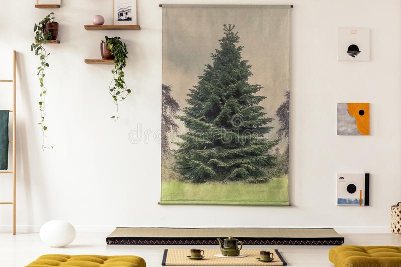 Real photo of a tree graphic hanging on white wall above a tatami mat in simple japanese interior with green tea set and yellow c. Ushions royalty free stock photos