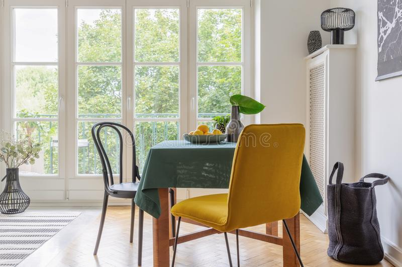 Vintage dining room interior with a table, yellow chair and big balcony window royalty free stock photo