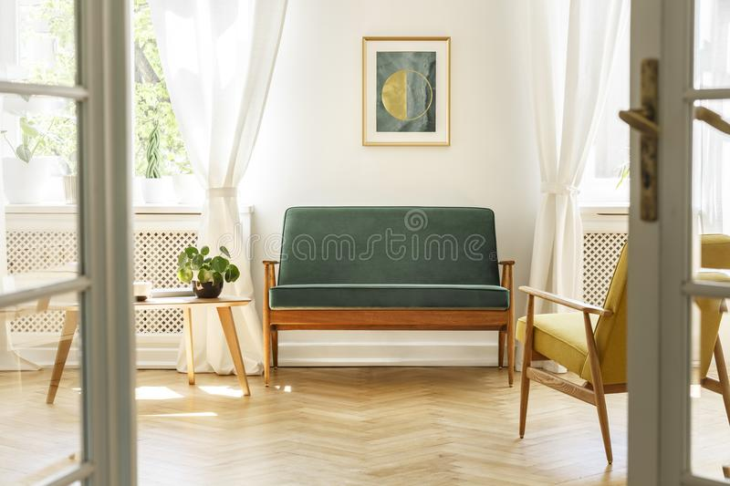 Real photo of a vintage living room interior with a green sofa,. Poster, coffee table, armchair and wooden floor. View through a door royalty free stock photography