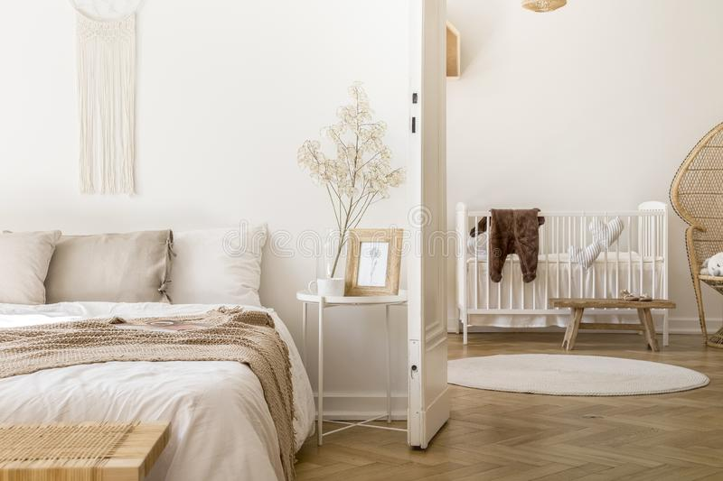 White bedroom interior with bedside table with plant, poster and mug and open door to baby room with rug and white c. Real photo of white bedroom interior with stock photos