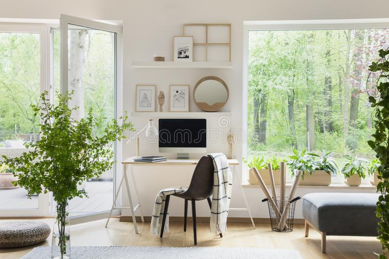 Real photo of white living room interior with big window, glass door, fresh plants, wooden desk with mockup computer and simple po. Sters on shelves concept stock photos