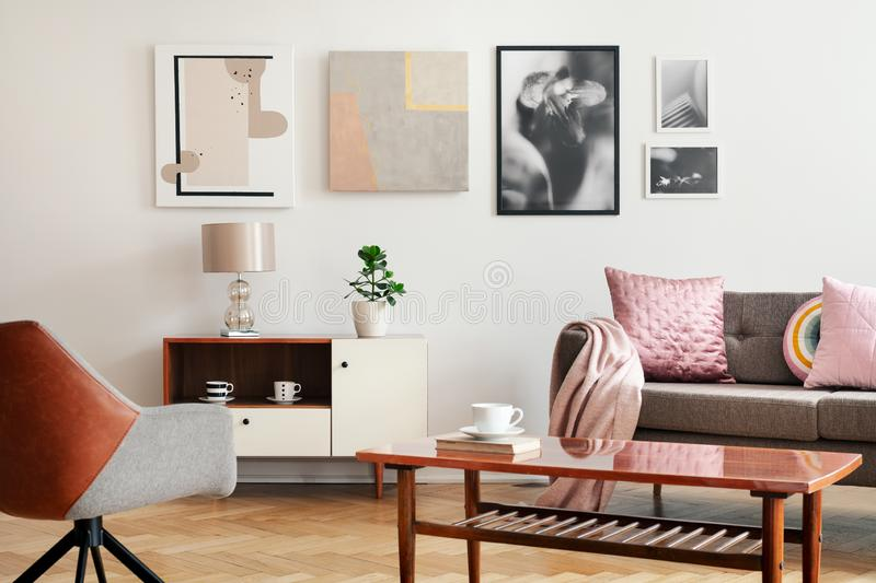 Real photo of white sitting room interior with poster on wall, couch with cushions and blanket, wooden coffee table with book and stock photo