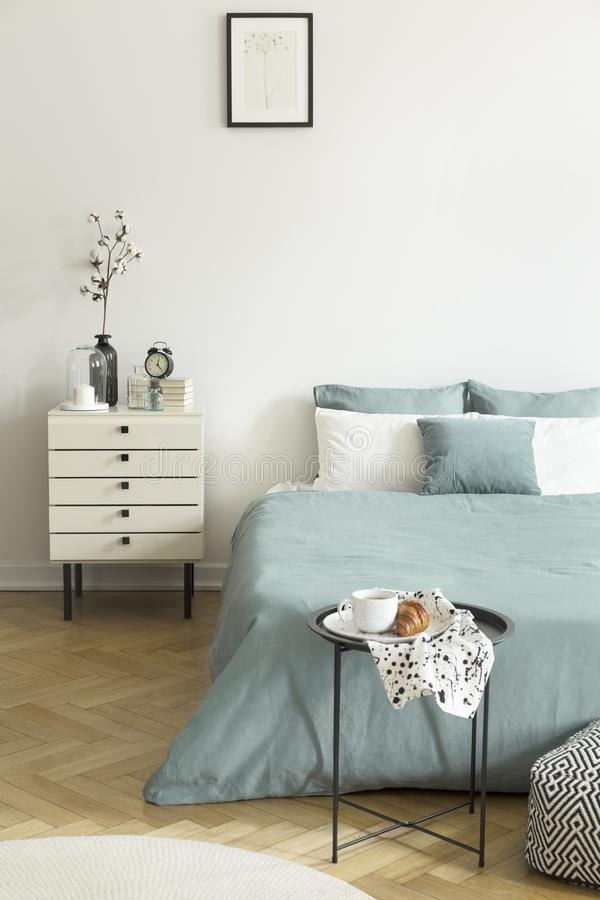 Real photo of a woman`s bedroom interior with white walls, parquet floor, pale sage green bedding and drawer cabinet. stock photography