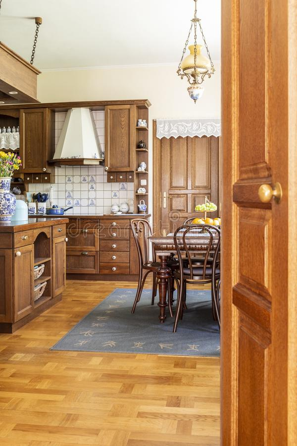 Real photo of a wooden kitchen interior with cupboards, dining t stock photo