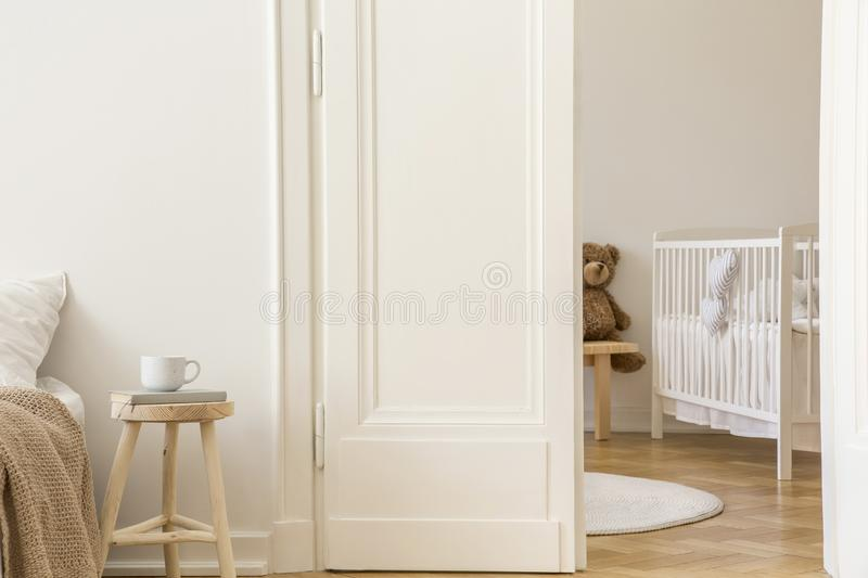Real photo of wooden stool with book and tea mug standing next to white door to kid room interior with crib. And herringbone parquet stock photography