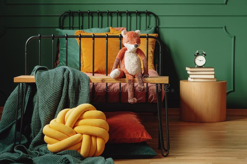 Real photo of a knot pillow, green blanket and plush fox on a wooden bench in front of a black bed in cute bedroom interior stock photos