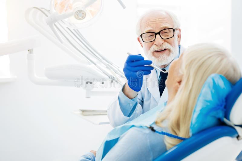 Skilled dentist inspecting patients mouth cavity royalty free stock photo