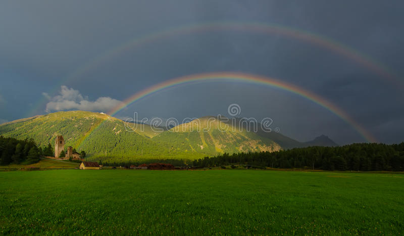 Real rainbow in a mountain meadow. Real full double rainbow in a mountain meadow stock images