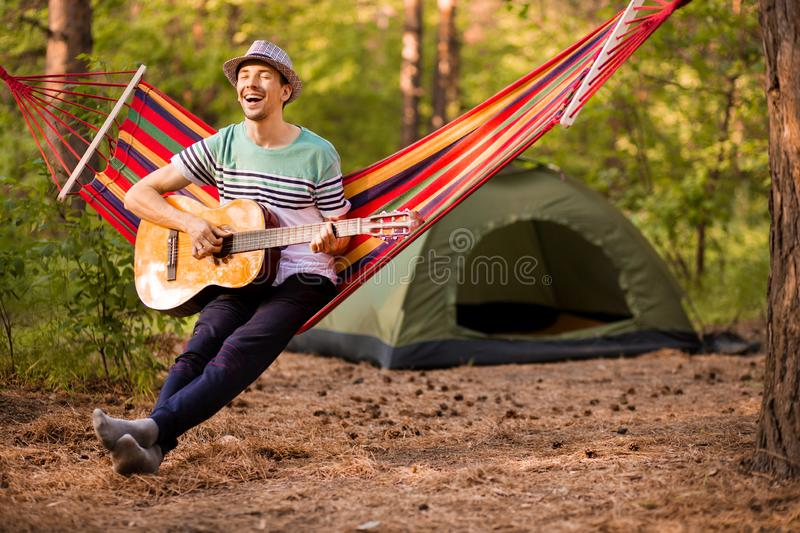 Real relaxation. Handsome young man in hat play guitar while lying in hammock stock images