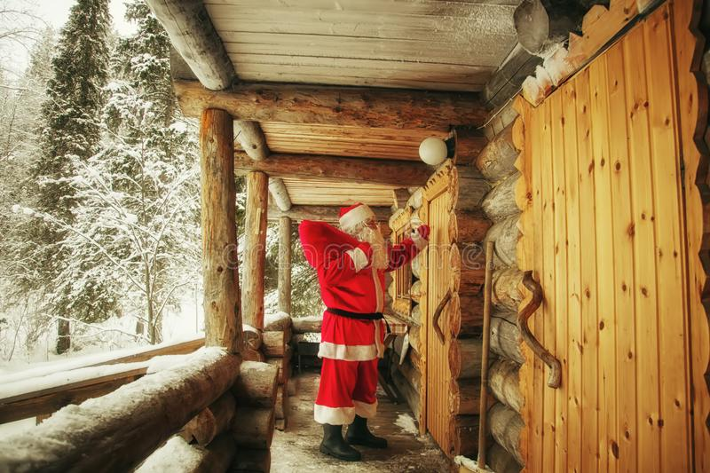 The real Santa Claus knocks on the door. The real Santa Claus knocks on the door of the hut in the winter forest royalty free stock photos