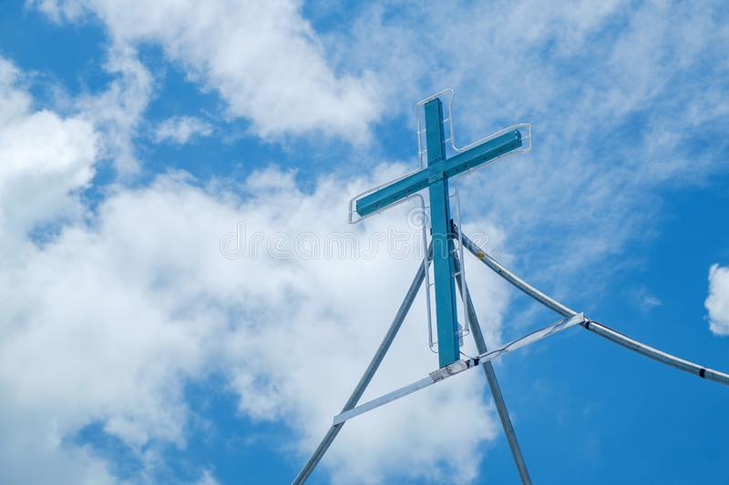 Real Simple Cross Sign with Light all Around in the Beautiful Cl. Ear Blue Sky with Clouds stock photo