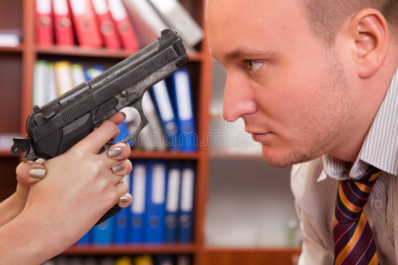 Real threat. Woman threatening man with gun at office royalty free stock photo