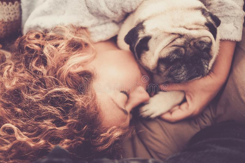 Real true love between middle age beautiful woman caucasian sleeping and protect, her best friends dog pug. friendship and. Relationship at home in the life stock photos