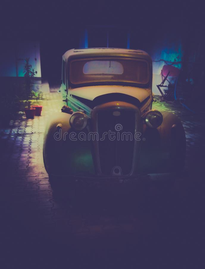 The real vintage car rwtro object shot in a garage with car in middle low light and dark black background at bordervintage days stock photo