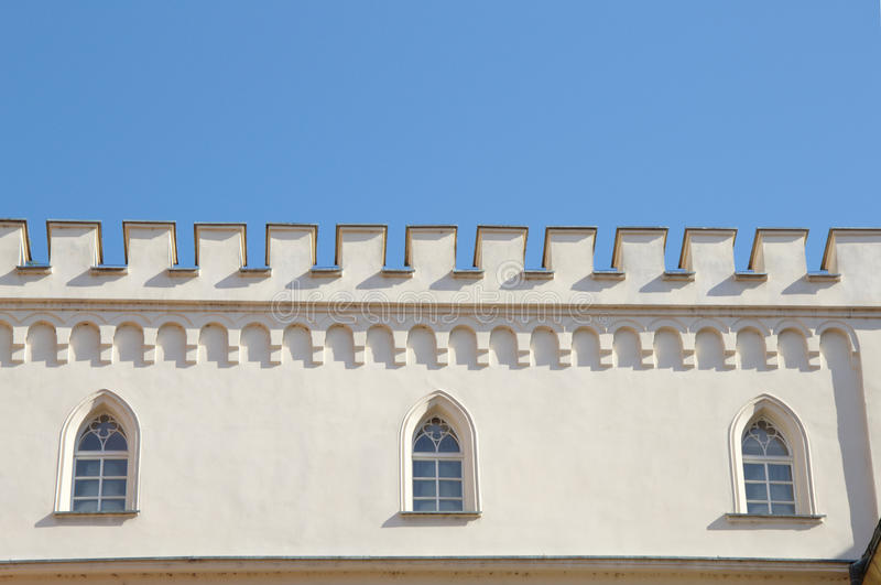 Real white castle wall with battlements and gothic windows stock images