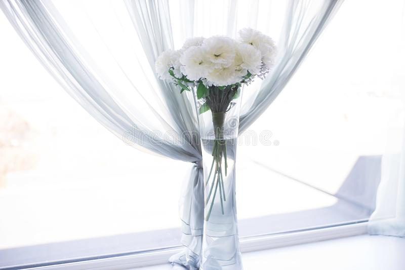 Vase with white flowers on the wedding day. Real white flowers in vase on the wedding day. Vase is on the table as decoration/ decor. Assian wedding hall/venue royalty free stock photo