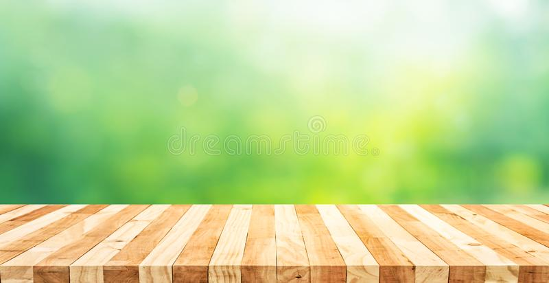 Real wood table top texture on blur fresh green garden background.For create product display or design key visual. Layout stock photos