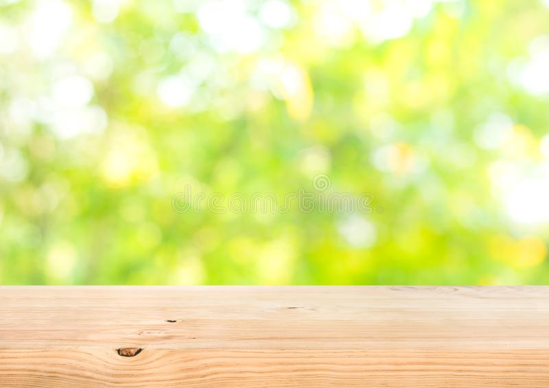 Real wood table top texture on leaf tree garden background. For create product display or design key visual layout stock photography
