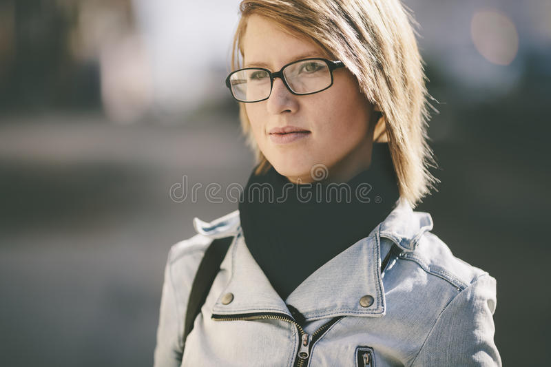 Real young woman with glasses going on the street royalty free stock photos