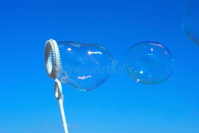 Reale Seifeluftblasen auf blauem Himmel lizenzfreie stockbilder