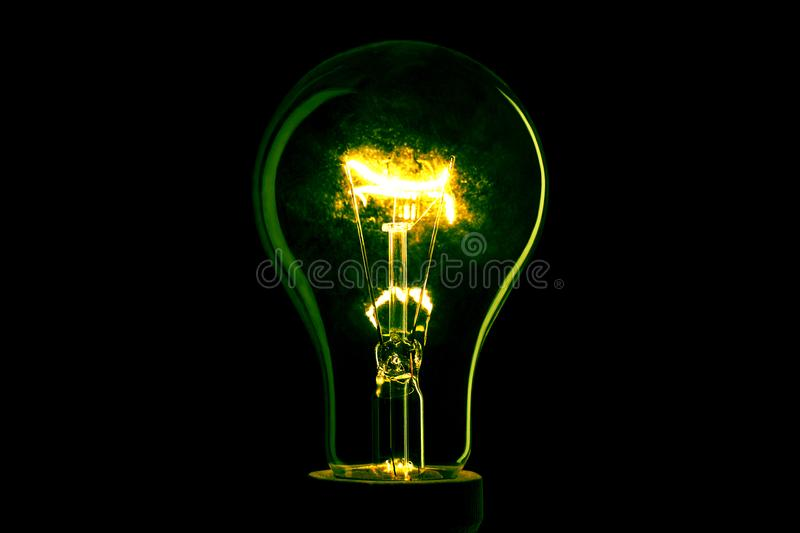 Abstract light bulb on the black background. Lamp light in the dark. Electric bulb. Glowing light in the dark. stock photography