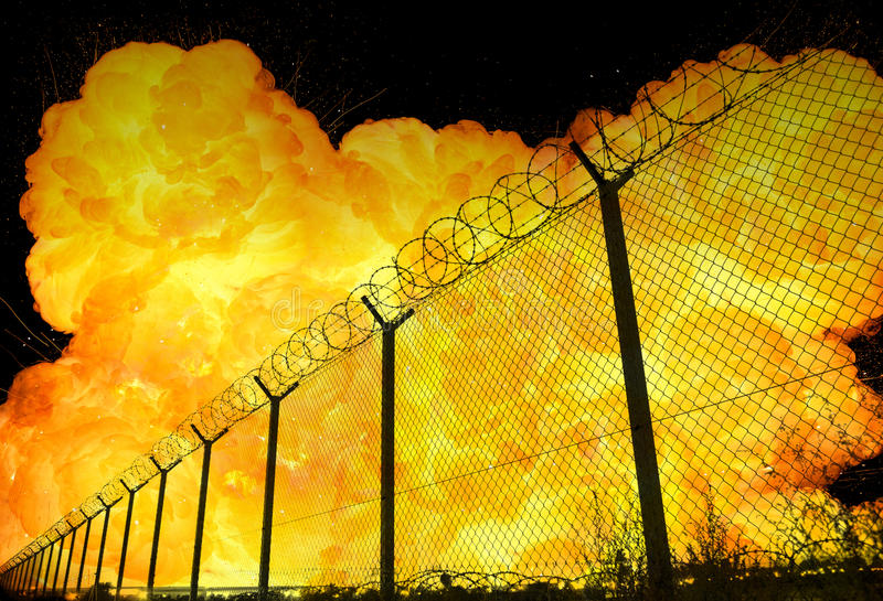 Realistic orange fire explosion behind restricted area barbed wire fence stock photos
