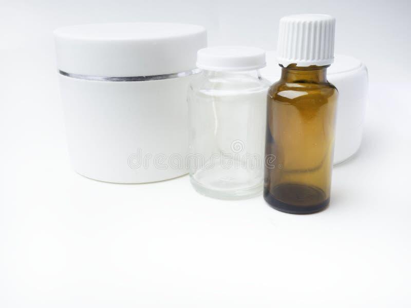 Realistisk brun flaska för nödvändig olja och vita behållare som är falska upp flaskan Kosmetisk liten medicinflaska, flaska, fla royaltyfri fotografi