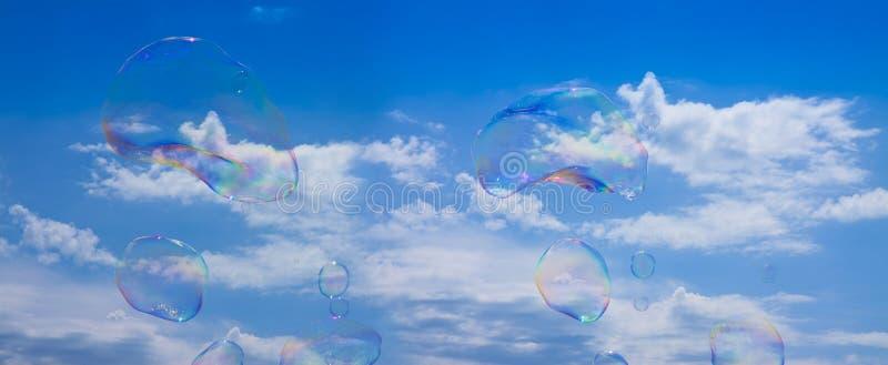 Realistiska såpbubblor gjorde med vatten- och tvålmaträtten som fladdrar på himmelbakgrund - begreppsbild arkivfoto
