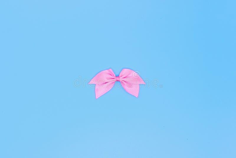 Realistiskt rosa band, pilbåge på en blå bakgrund, begreppet av ett feriekort royaltyfria foton