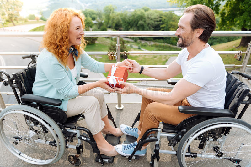 Realitet wheelchaired par som rymmer en gåva arkivfoton