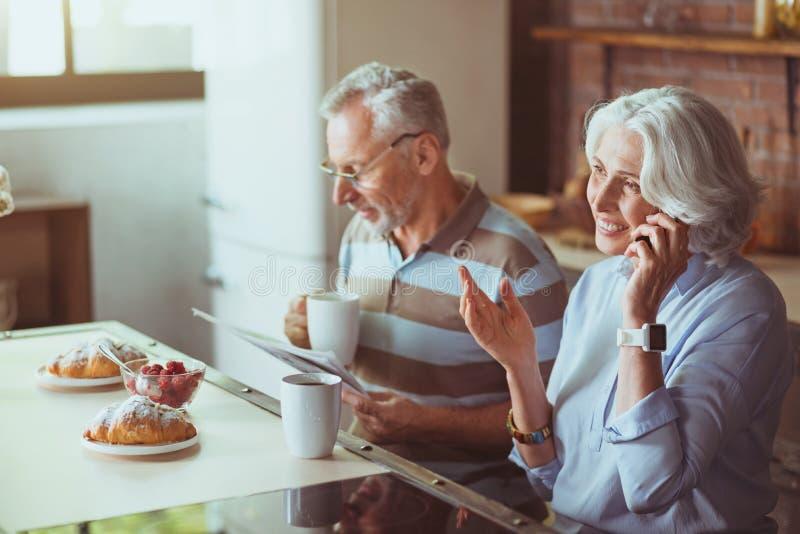 Realiteten åldrades par som har frukosten i köket royaltyfria bilder