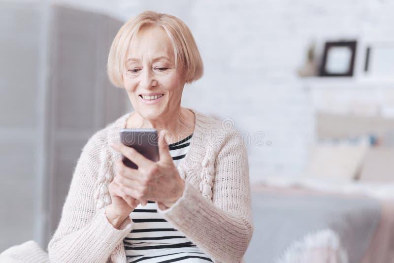 Realiteten var besvärad den höga damen som ser skärmen av hennes smartphone royaltyfri foto