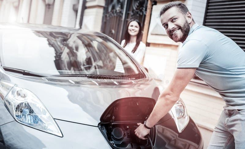 Realiteten var besvärad mannen som ler, medan ladda hans miljövänliga bil arkivfoto