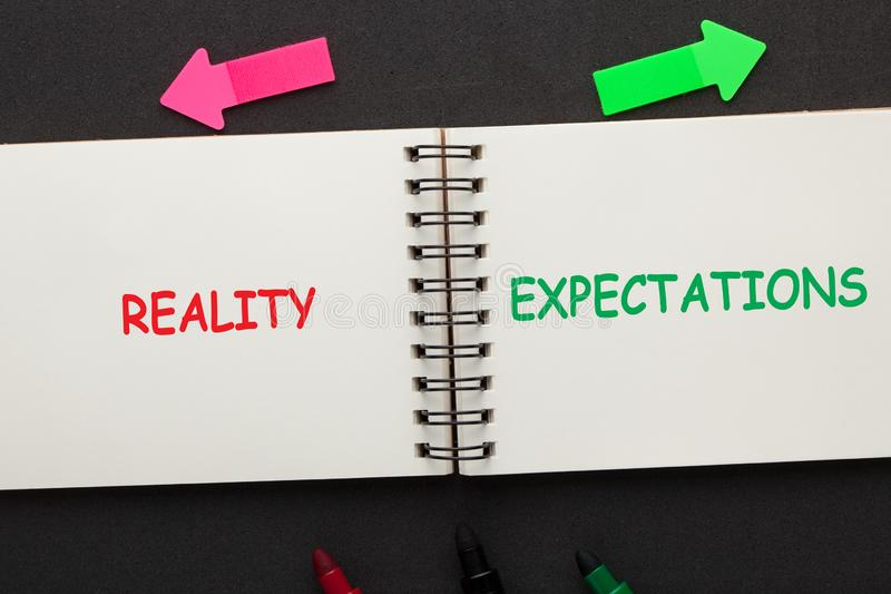 Reality Expectations Concept. The words Reality vs Expectations written on open spiral notebook and various stationery. Business concept stock photos