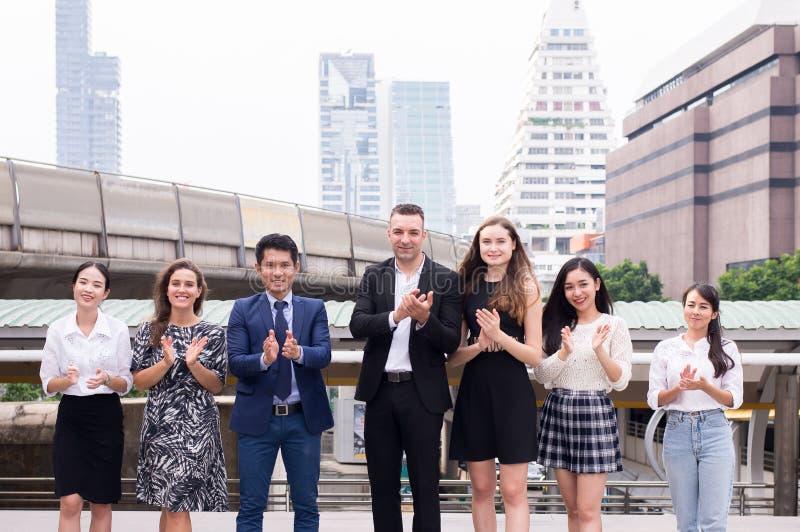 A realização do sucesso da equipe aplaude seus mãos, grupo bem sucedido de povos da diversidade do negócio, fusões e aquisição foto de stock royalty free