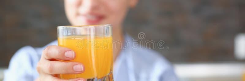 Realizar bonito da mulher no vidro dos braços do suco de laranja fotos de stock royalty free