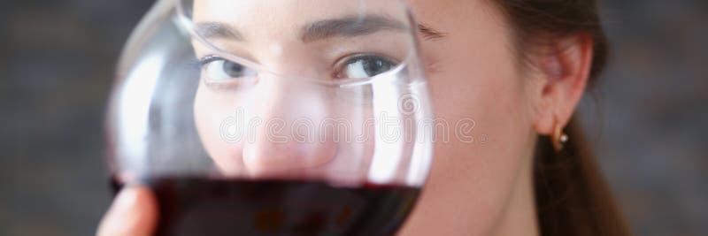 Realizar bonito da mulher no vidro dos braços do vinho tinto imagem de stock royalty free