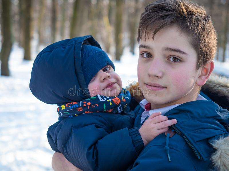 Realizar do irmão mais velho nos braços seu irmão novo no fundo do parque do inverno imagens de stock royalty free