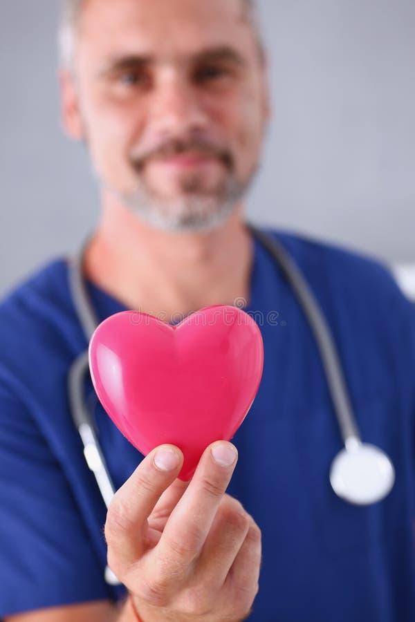 Realizar masculino do doutor no coração do vermelho dos braços foto de stock