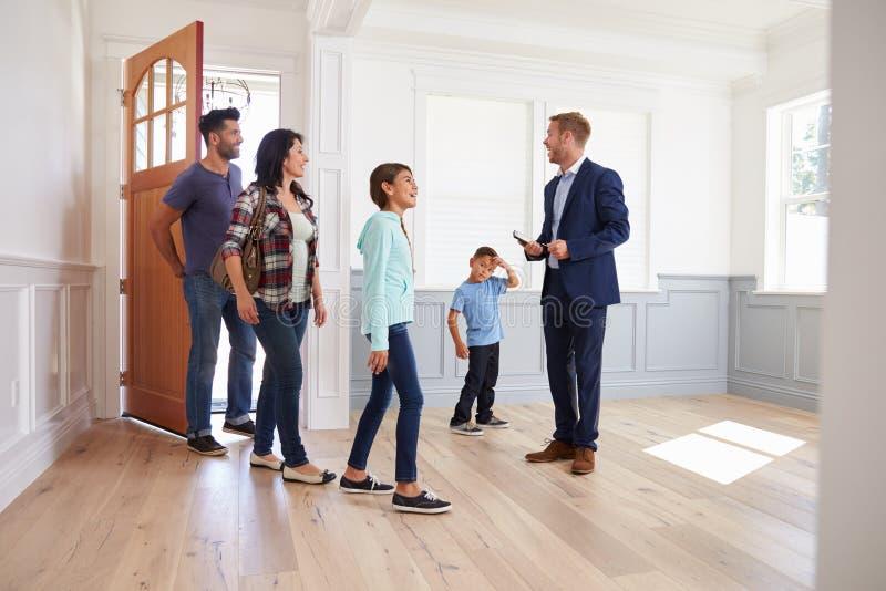 Realtor που παρουσιάζει ισπανική οικογένεια γύρω από το νέο σπίτι στοκ εικόνα