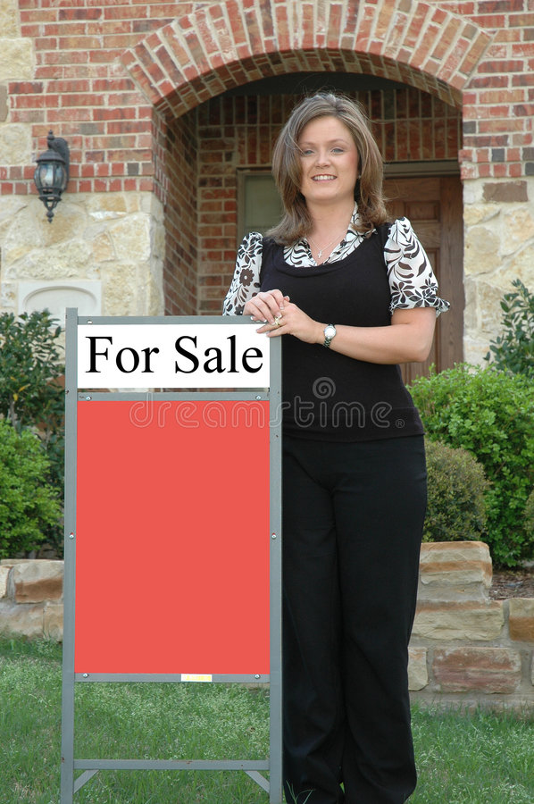 Realtor. Real Estate agent standing in front of a home with a for sale sign. Bottom part of sign is blank to fill in with your own information royalty free stock image