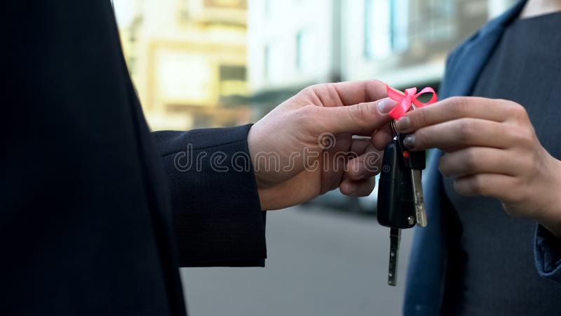 Realtor agent giving lady keys to new apartment, loan repayment, house mortgage. Stock photo royalty free stock images