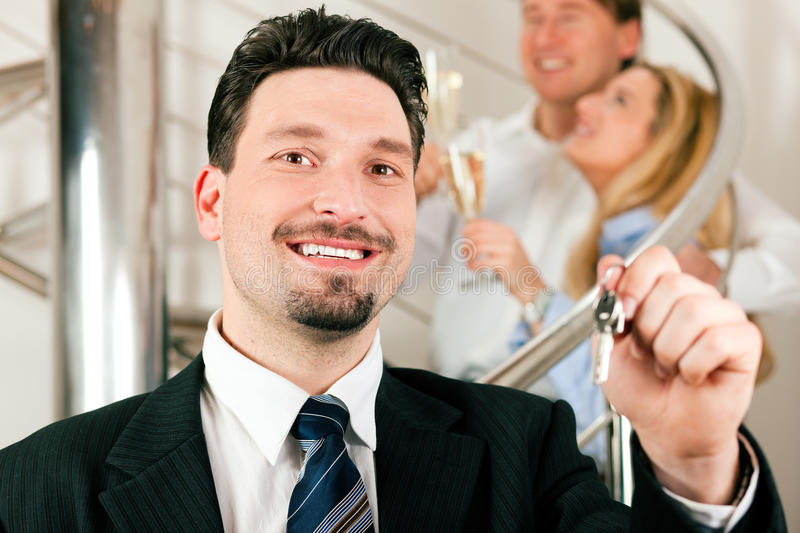 Realtor In Apartment Giving Keys To Couple Royalty Free Stock Photos
